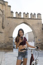 Spain, Baeza, portrait of smiling young woman with bicycle looking at cell phone - JASF01976