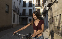 Spain, Baeza, portrait of smiling young woman with bicycle in the city - JASF01979