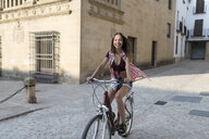 Spain, Baeza, smiling young woman riding bicycle in the city - JASF01982