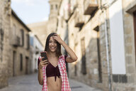Spain, Baeza, portrait of smiling young woman with cell phone - JASF01985