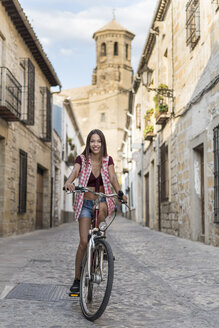 Spain, Baeza, portrait of smiling young woman riding bicycle in the city - JASF01988