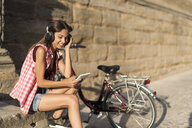 Spain, Baeza, relaxed young woman with headphones looking at digital tablet - JASF01991