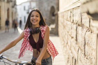 Spain, Baeza, portrait of laughing young woman pushing her bicycle in the city - JASF01994