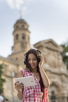 Spain, Baeza, portrait of smiling young woman using headphones and digital tablet in the city - JASF01997