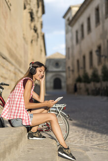 Spain, Baeza, relaxed young woman with headphones looking at digital tablet - JASF02000