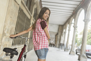 Spain, Baeza, portrait of smiling young woman pushing bicycle in the city - JASF02003