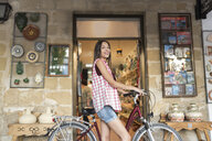 Spain, Baeza, portrait of miling young woman with bicycle in front of gift shop - JASF02006