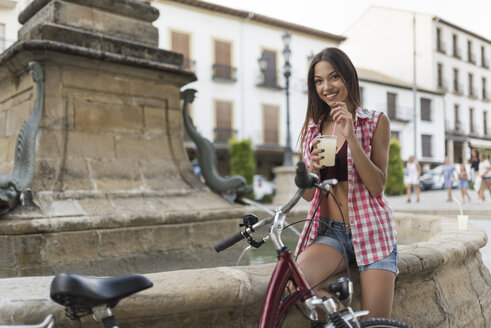 Spain, Baeza, portrait of smiling young woman with bicycle drinking lemon granita in the city - JASF02009