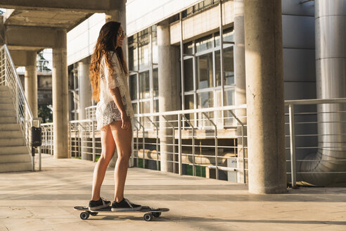 Young woman riding skateboard in the city - KKAF02481