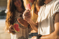 Close-up of friends eating watermelon slices outdoors - KKAF02484