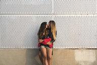 Lesbian couple hugging at a wall - KKAF02493