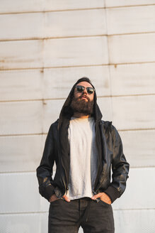 Cool bearded young man wearing sunglasses and hooded jacket - KKAF02496