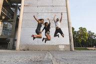 Exuberant friends jumping outdoors - KKAF02499