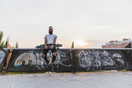 Cool bearded young man with skateboard outdoors - KKAF02505