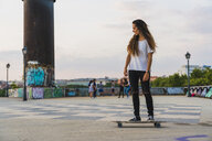 Young woman riding skateboard in the city - KKAF02517