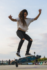 Young woman doing a skateboard trick in the city - KKAF02520