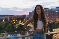 Beautiful smiling young woman with long brown hair in the city at dusk - KKAF02532