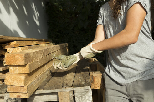 Craftswoman putting on protective gloves at a pile of wood - JPTF00037