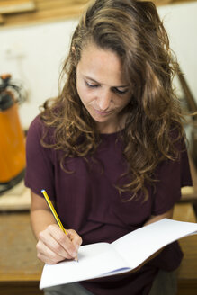 Craftswoman taking notes in her workshop - JPTF00046