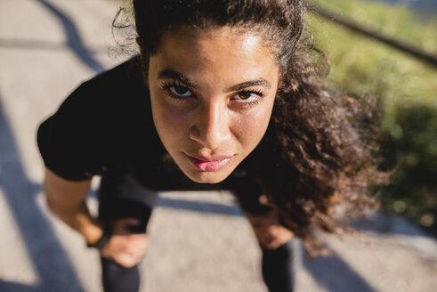 Portrait of sportive young woman having a break - FMOF00383