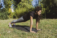 Sporty young woman doing push-ups on a meadow - FMOF00392