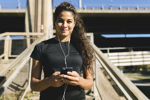 Portrait of sporty young woman having a break listening to music - FMOF00401