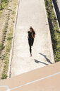 Sportive young woman running on a path - FMOF00404