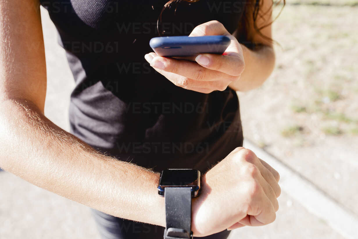 Close-up of sporty young woman using cell phone and smartwatch - FMOF00410 - Francesco Morandini/Westend61