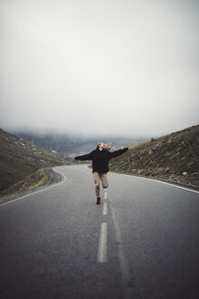 Blonde woman running on a road with mountains in the background - ACPF00365