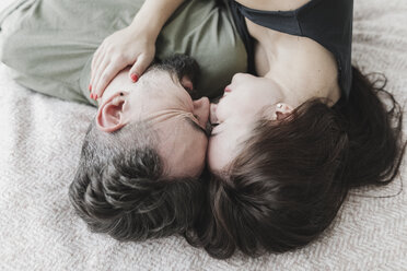 Couple lying on bed, kissing, cuddling and embracing - KMKF00588