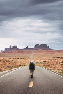 USA, Utah, Man with backpack walking on road to Monument Valley - KKAF02540