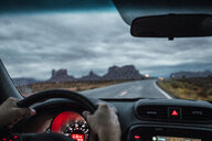 USA, Utah, Car driving to Monument Valley under a stormy sky - KKAF02549