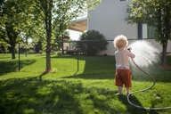 Rear view of shirtless baby boy spraying water on grassy field with hose at yard - CAVF50530