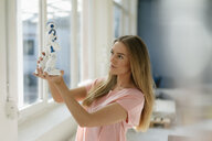 Portrait of young woman looking at toy robot - KNSF04999