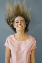 Portrait of smiling young woman tossing her hair - KNSF05002