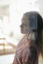 Portrait of pensive young woman behind glass pane - KNSF05005