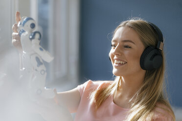 Portrait of smiling young woman with headphones looking at toy robot - KNSF05020