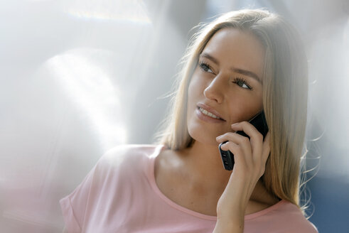 Portrait of smiling young woman on the phone - KNSF05026
