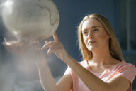 Portrait of young woman looking and pointing at globe - KNSF05029