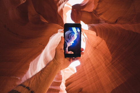 USA, Arizona, tourist in Lower Antelope Canyon, photo on smartphone - KKAF02555