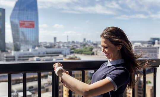 UK, London, happy woman using smartwatch on a roof terrace - MGOF03807