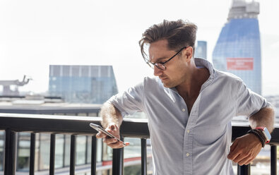 UK, London, man using cell phone on a roof terrace - MGOF03816