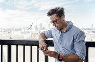 UK, London, man using cell phone on a roof terrace - MGOF03819