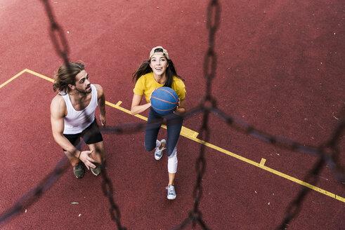Young man and woman playing basketball on basketball ground - UUF15557