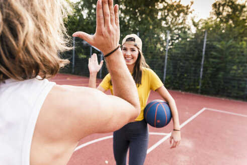 Young man and young woman high-fiving after basketball game - UUF15560