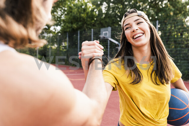 Young man and young woman high-fiving after basketball game - UUF15563 - Uwe Umstätter/Westend61