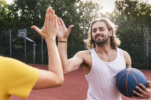 Young man and young woman high-fiving after basketball game - UUF15566
