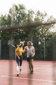 Young couple having fun on the basketball ground - UUF15569