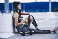 Young woman sitting on ground after dumbbell training, drinking juice - UUF15596