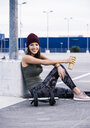 Young woman sitting on ground after dumbbell training, drinking juice - UUF15599